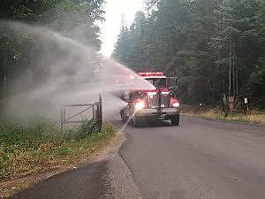This Coram-West Glacier Fire Engine sprayed water along Going-to-the-Sun Road yesterday in an effort to raise the humidity in the area. (NPS Photo)