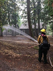 A firefighter soaks the ground around buildings near Lake McDonald Lodge to raise humidity in the immediate area. (NPS Photo)