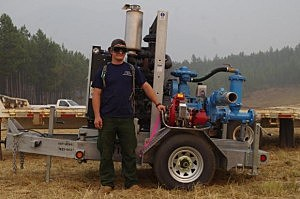Bobby Freeman, Camp Crew Member, with a three inch pump from Rain for Rent and one of the one and a half inch pumps it will be placing on Lake McDonald Lodge area. (NPS Photo)